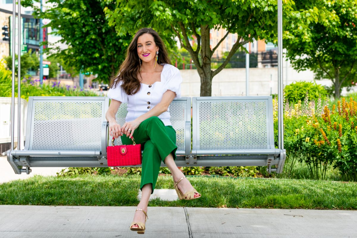 Green pants with pink wicker handbag