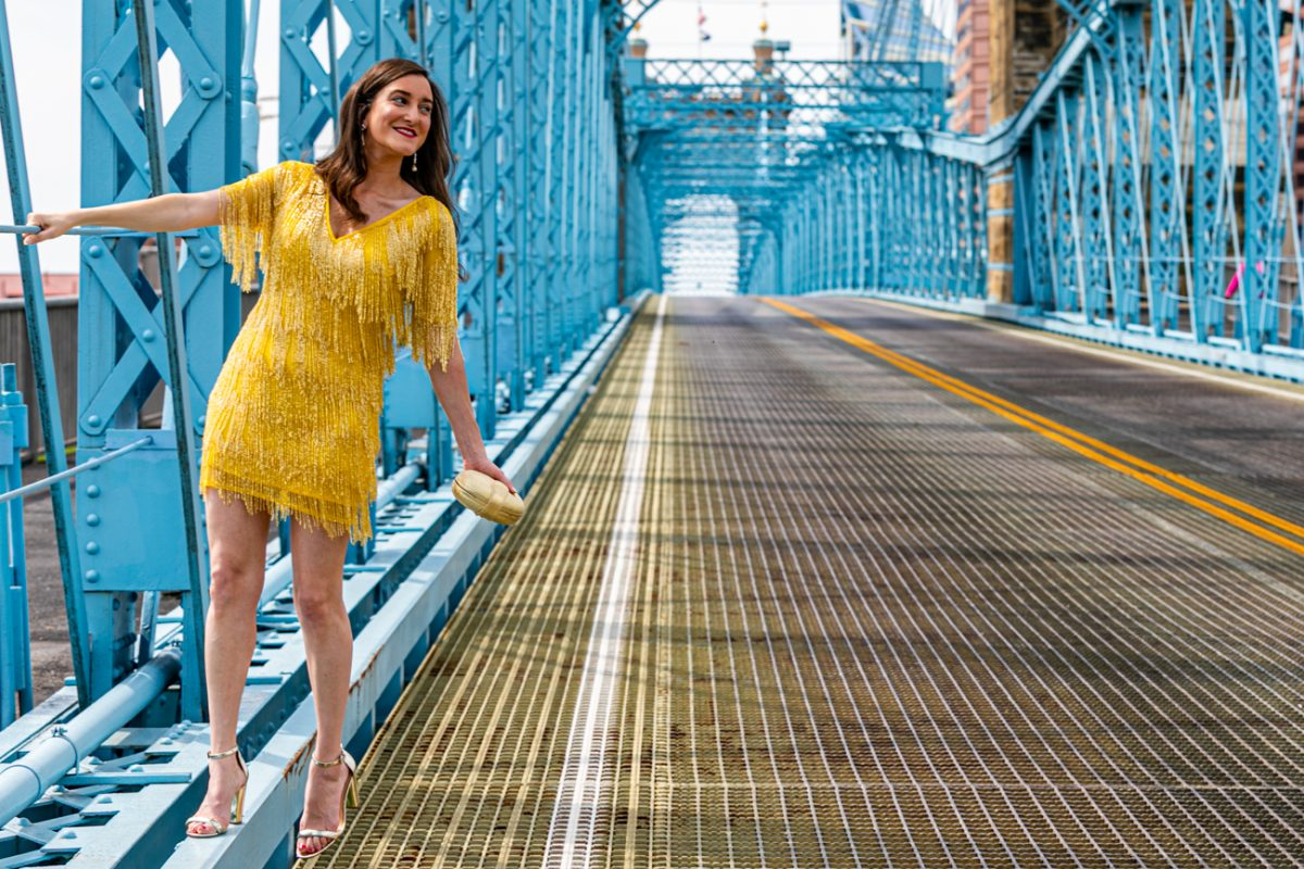Cincinnati fashion blogger Olivia Johnson wearing a yellow beaded dress on the Roebling Bridge