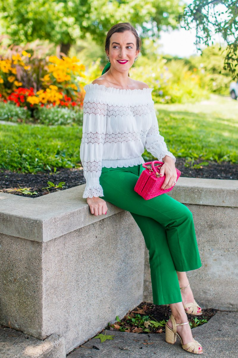 girl wears a pink wicker handbag and green pants and a velvet bow